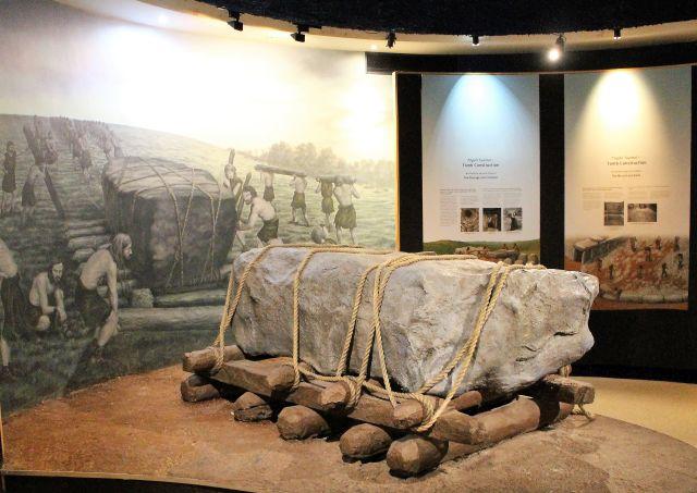 Blick in einen Museumsraum im Besucherzentrum für Newgrange. Ein Felsbrocken liegt auf Holzstämmen.