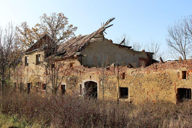 Ruine eines Bauernhofs aus Backsteinen. Das Dach ist weitgehend eingefallen.