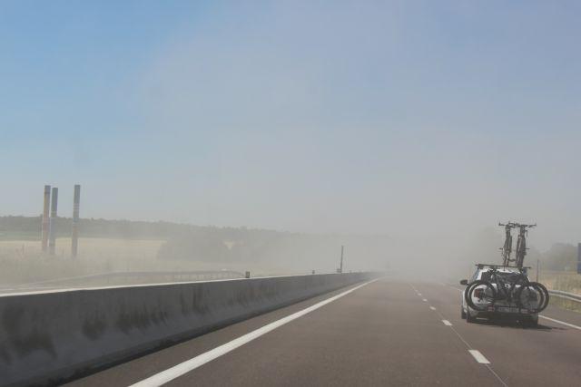 Staubwolken über einer Autobahn. Links und rechts Ackerflächen.