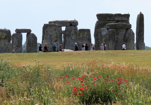 Der Steinkreis Stonehenge. Querliegende Steine auf hohen Steinen. Im Vordergrund grünen Wiese mit Mohnblumen.