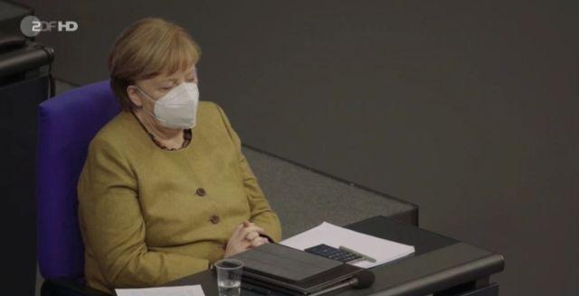 Angela Merkel in der Regierungsbank im Bundestag mit weißer Corona-Maske. Sie hat für längere Zeit die Augen zu.