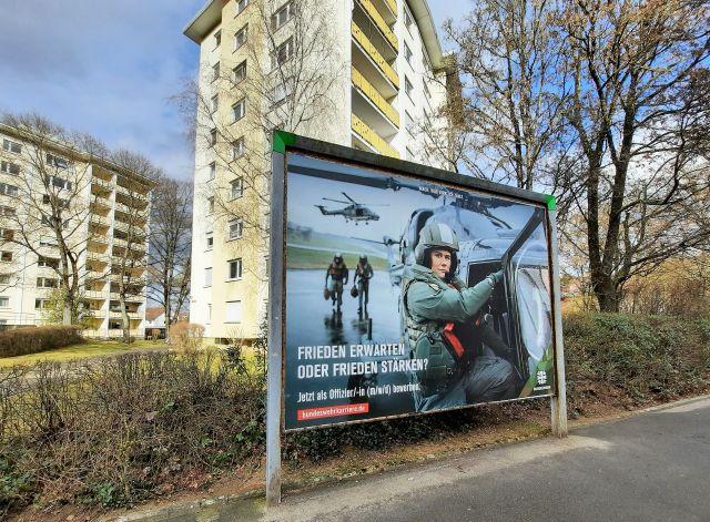 Plakat der Bundeswehr zur Gewinnung von Offizieren. Eine Soldatin steigt in einen Hubschrauber. Hinter dem Plakat zwei Wohngebäude.