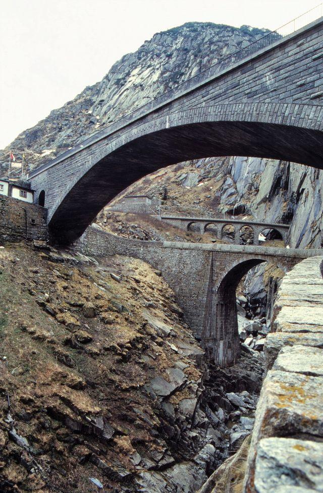 Am Gotthard sind mehrere steinerne Brücken zu sehen, über die kleine Straßen bzw. eine Bahnlinie führen.