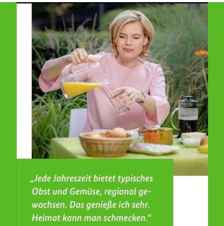 """Julia Klöckner, blonde Haare, sitz im Freien an einem Tisch. Sie gießt gerade Orangensaft ein. Zu sehen sind Kaffee, Brötchen, eine Banane und ein Apfel. Text: """"Jede Jahreszeit bietet typisches Obst und Gemüse, regional gewachsen. Das genieße ich sehr. Heimat kann man schmecken."""""""