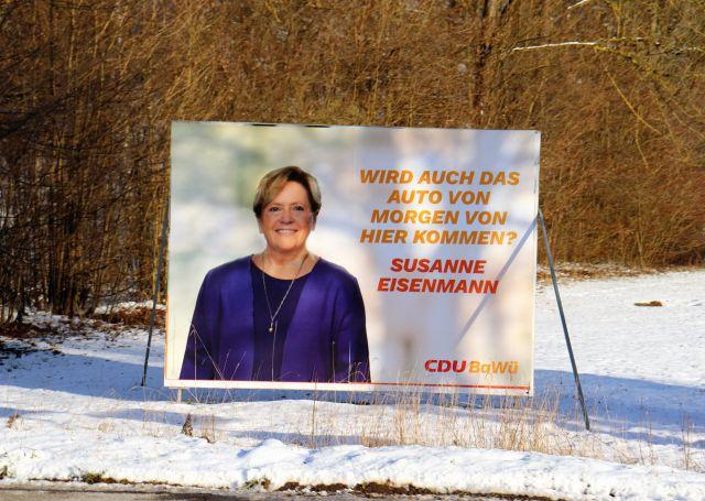 """Plakat mit der CDU-Spitzenkandidatin Susanne Eisenmann. Sie trägt blauviolette Kleidung Das Plakat steht im Schnee. Text: """"Wird auch das Auto von morgen von hier kommen?"""""""