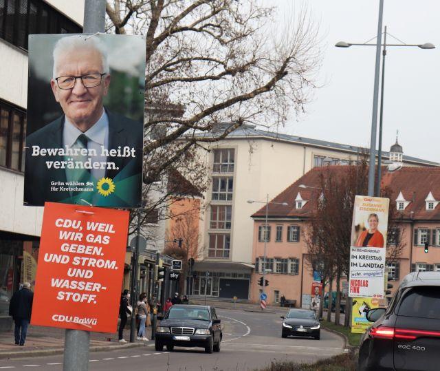 """Wahlplakate an einer Straße in Esslingen. Vorne ein Plakat mit Winfried Kretschmann. Text: """"Bewahren heißt verändern"""". Darunter Plakat der CDU. Text: """"CDU. Weil wir Gas geben. Und Strom. Und Wasserstoff."""""""