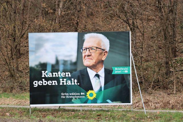 """Wahlplakat mit Winfried Kretschmann, weiße Haare, Brille. Text: """"Kanten geben Halt""""."""
