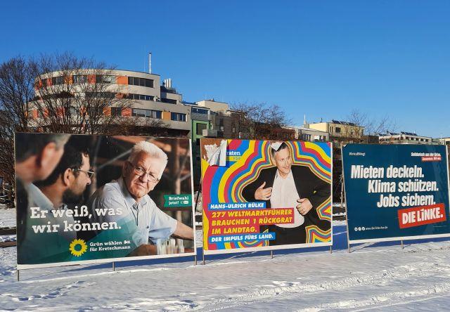 Drei Großplakate im Schnee, dahinter Wohngebäude. Links die Grünen, denn FDP und Die Linke. Hans-Ulrich Rülke, FDP ist debei, sein Jackett anzuziehen.