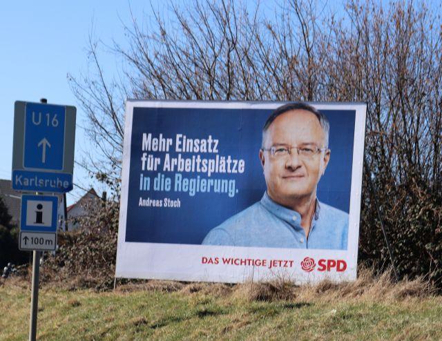 """Großplakat der SPD mit dem Spitzenkandidaten Andreas Stoch im blauen Hemd. Text: """"Mehr Einsatz für Arbeitsplätze in die Regierung"""". Das Plakat steht auf einer Grünfläche, dahinter ein Strauch. Linke ein Schild wie es für Umleitungsstrecken vorgesehen ist."""