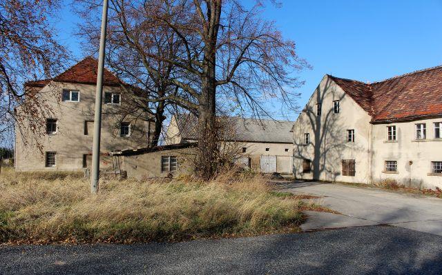 Leerstehendes Gebäude mit Garagen und Anbauten, das früher landwirtschaftlich genutzt wurde.