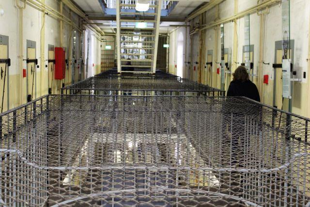 Blick in eine Ebene des früheren Stasi-Gefägnisses in Bautzen, heute eine Gedenkstätte. Schwere Zellentren und ein stabiles Netz sind zu sehen, das Gefangene am Sprung in die Tiefe hindern sollte.