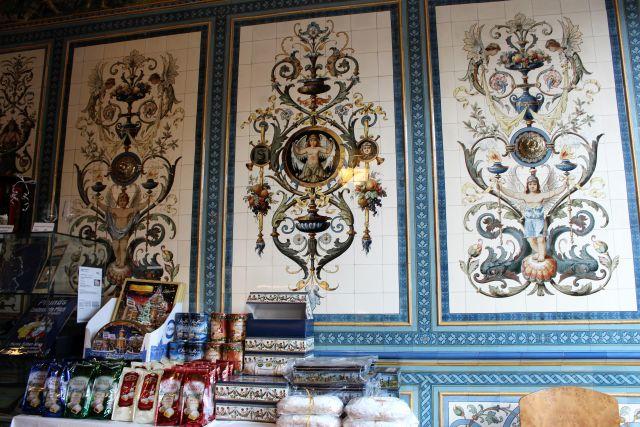 Künstlerisch bemalte Wandfliesen. Davor Produkte aus der Region wie z. B. Dresdner Stollen.