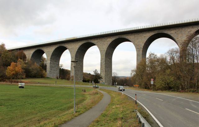 Mehrere Bögen der Brücke über das Elstertal sind zu sehen. Die Brücke ist mit Natursteinen verkleidet. Im Vordergrund links eine grüne Wiese, rechts eine Straße mit einem Fahrzeug.