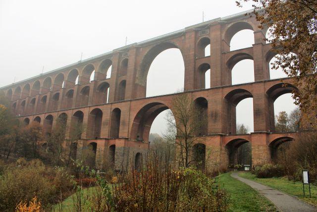 Die aus roten Backsteinen gemauerte Göltzschtalbrücke im leichten Nebel. Vier Bogenreihen stehen aufeinander.