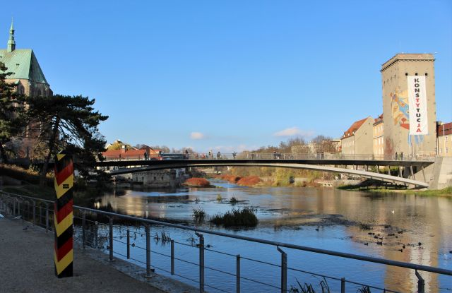 Eine filigrane Brücke spannt sich über die Lausitzer Neiße. Links ein Grenzpfahl mit den deutschen Farben schwarz, rot, gold. Rechts an einem bunt bemalten Turm auf polnischer Seite ein Transparent. In Großbuchstaben heißt es: Konstytucja - Verfassung.