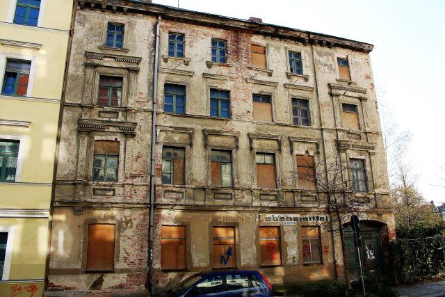 Eine Hausfassade in sehr schlechtem Zustand. Links ist ein renoviertes Hausteil zu sehen.