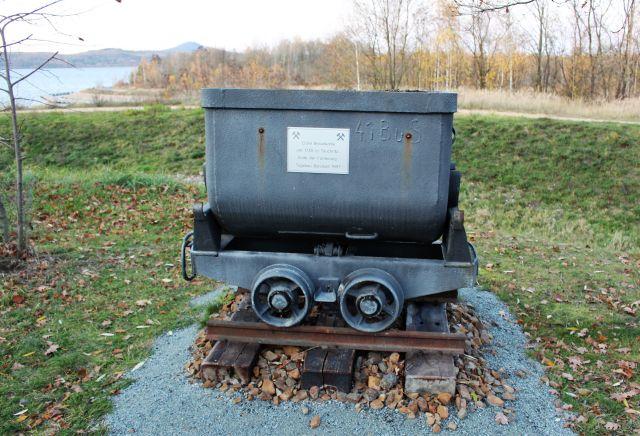 Eine Lore auf einem kurzen Schienenstück mit unterlegtem Schotter. Text auf der Lore: Erste Braunkohle um 1735 in Tauchritz – Ende der Förderung Tagebau Berzdorf 1997.