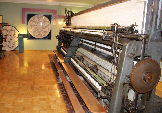 Eine mehrere Meter lange Stickmaschine. Im Hintergrund eine gestickte Tischdecke.
