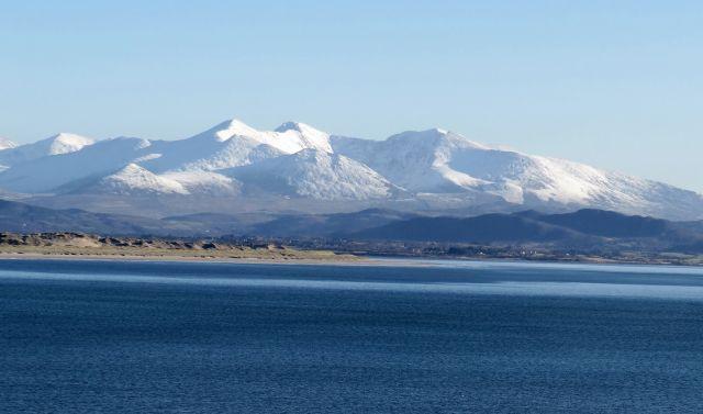 Berge direkt am Meer mit leichter Schneedecke. Weiter unten an der Küste liegt kein Schnee. Das Meer schimmert blau.
