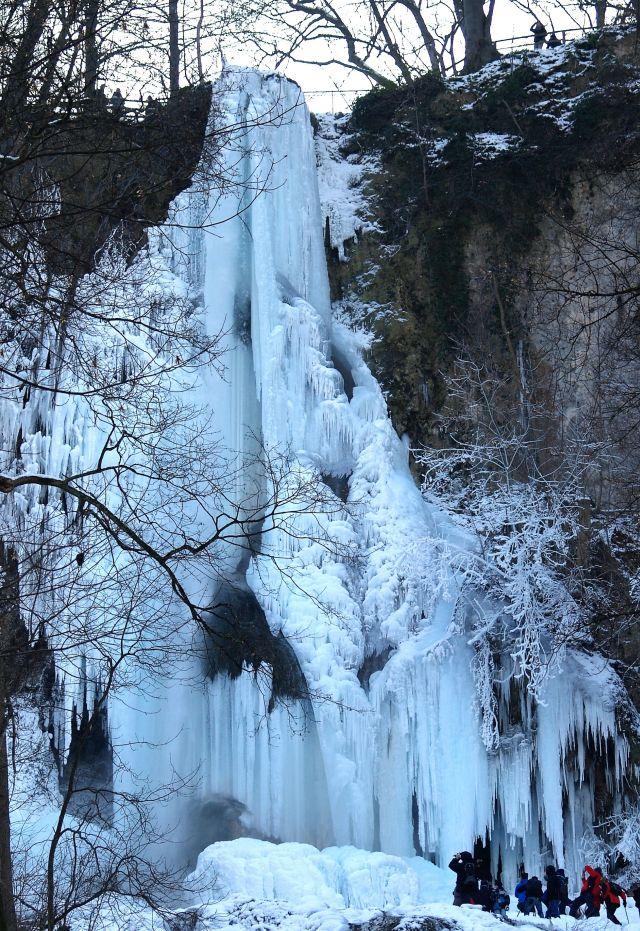 Der Uracher Wasserfall ist in einem kalten Winter vollkommen vereist. Das Eis zieht sich von der Abbruchkante über viele Meter bis zum Talboden.