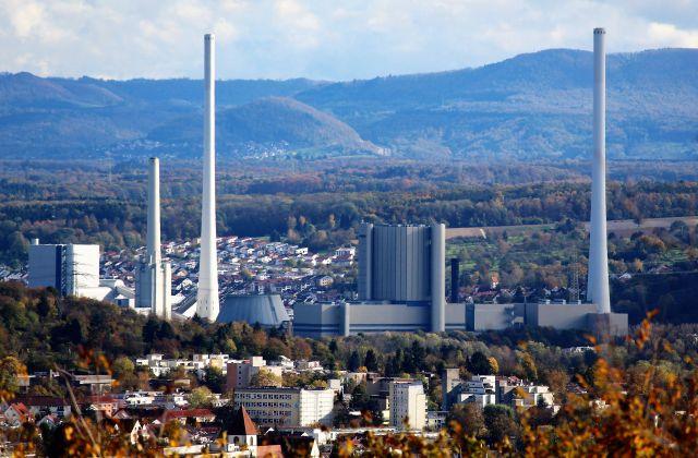Konventionelles Kraftwerk mit mehreren hohen weißen Kaminen. Es ist umgeben von Wohnbebauung.