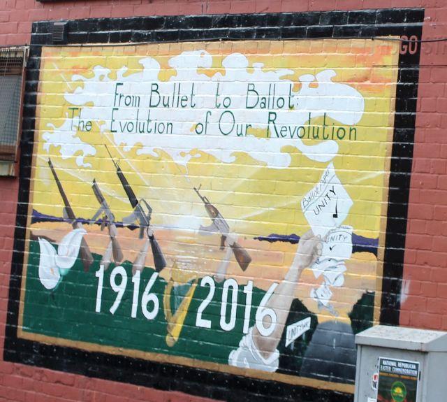 """Ein Mural - Wandgemälde - in Belfast mit dem Text """"From Bullet to Ballot. The Evolution of Our Revolution"""". Links im Bild Schnellfeuergewehre, rechts Wahlzettel."""
