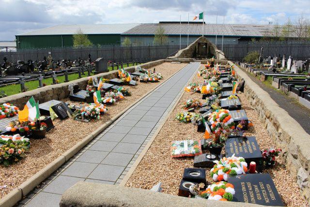 Friedhof mit Gräbern, die mit der irischen Flagge - Trikolore mit den Farben Grün, Weiß und Orange - geschmückt sind,