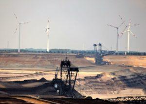Im Vordergrund gewaltige Bagger, die in dunkler Braunkohle graben. Im Hintergrund obethalb des Tagebaus Windrotoren.