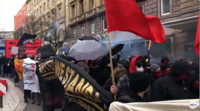 Linksextreme Demonstranten sind vermummt. Rote Fahnen.