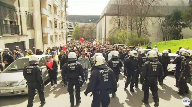 Polizisten gehen rückwärts vor dem Demonstrationszug her. Sie tragen weiße Schutzhelme. Die Demonstranten gehen eng gedrängt.