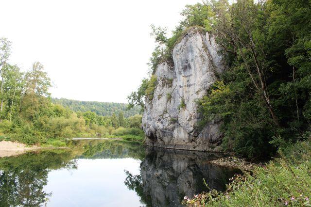 Ein steiler Felsen erhebt sich über einen Fluss, die Donau.