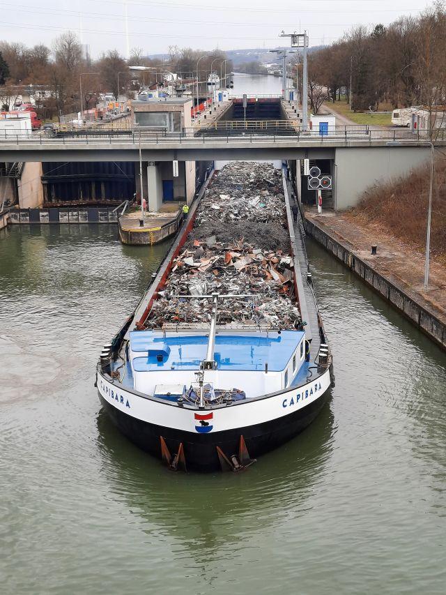 Ein Binnenschiff, das nur ganz knapp in die Schleuse passt, fährt wieder auf den Fluss. Das Schiff ist mit Schrott beladen.
