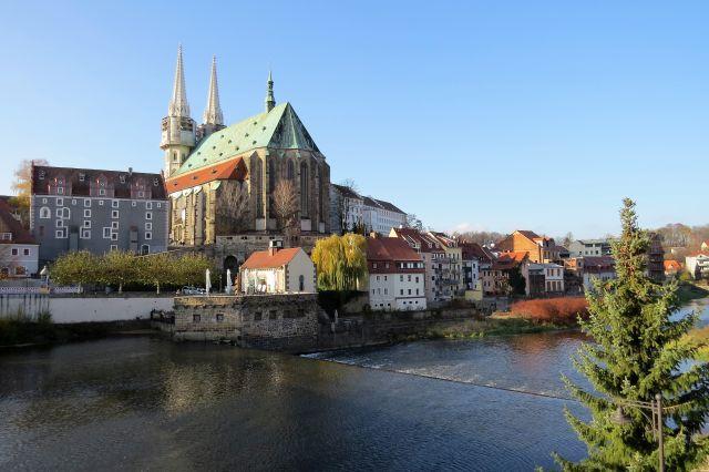 Kirchenbau mit grünem Dach weit oberhalb eines Flusses, die Lausitzer Neiße.
