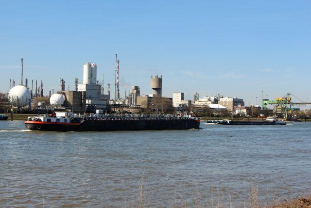 Zwei Binnenschiffe begegnen sich auf dem Rhein. Im Hintergrund ein Chemieunternehmen mit Tanks und anderen Produktionsanlagen.