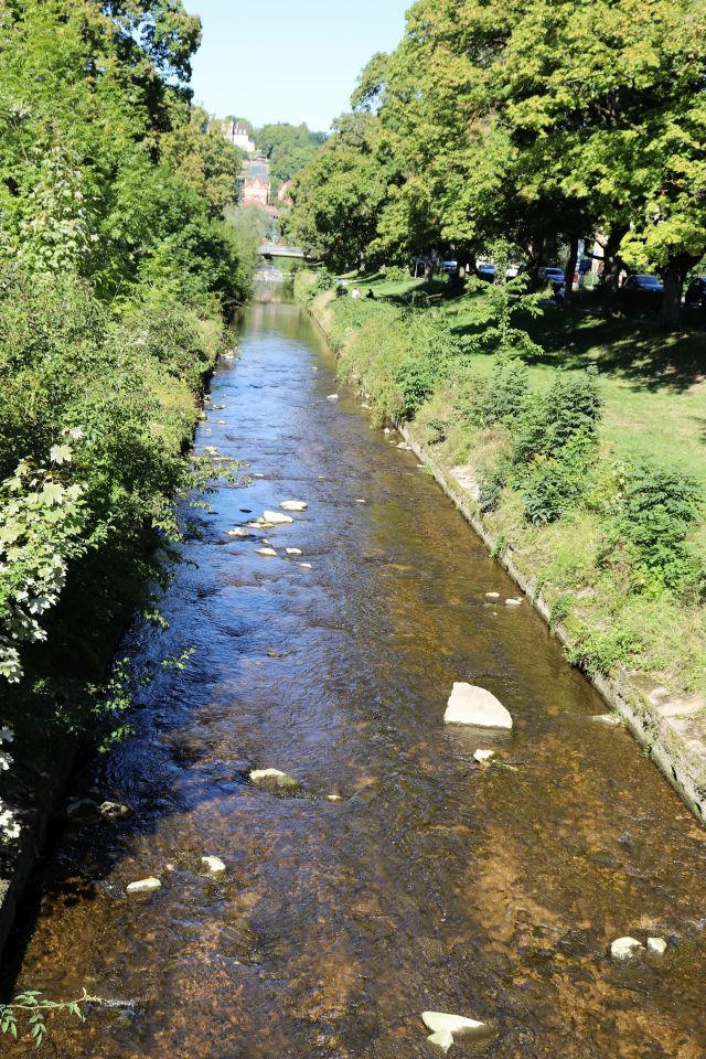 Ein kleiner Fluss - die Steinlach - ist in ein Betonkorsett gezwängt. Links und rechts Gras und Büsche.