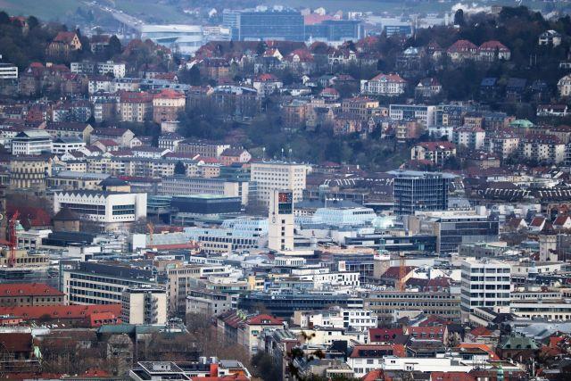 Blick auf die Innenstadt von Stuttgart. Die Stadt liegt in einem Talkessel. In der Mitte des Bildes der helle Turm des Rathauses.