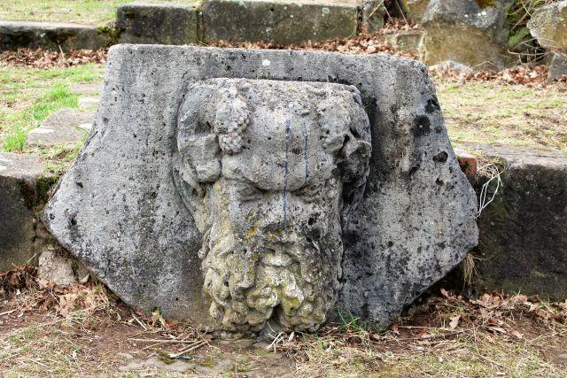 Ein in Stein gehauener bärtiger Kopf mit Locken.