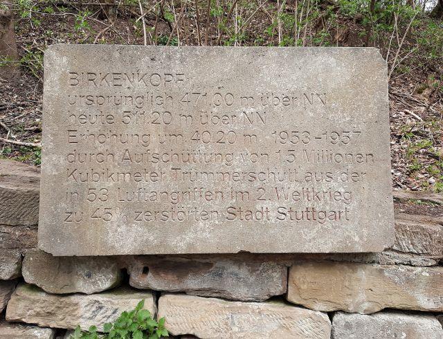 Informationstext in Stein gehauen. zum Inhalt des Textes: Der Birkenkopf wuchs durch die Trümmer um 40 Meter auf 511 Meter an und bekam im Volksmund den Namen Monte Scherbelino. Von 1953 bis 1957 wurden 1,5 Mio. m³ an Schutt aus der zu 45 % zerstörten Stadt heraufgefahren, die unter 53 Luftangriffen schwer gelitten hatte.