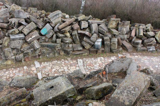 Blick von höhergelegenen Trümmerteilen auf den Weg zwischen zwei Hügeln aus Schutt. Der Boden ist mit Steinen und Platten aus zerstörten Gebäuden belegt.