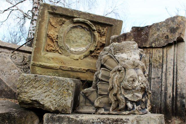 Trümmerteile aus bräunlichem und grauem Gestein. Darunter ein Löwenkopf.