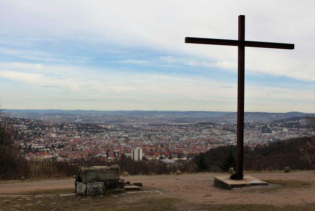 Ein hohes Metallkreuz rechts im Bild, links eine Kanzel aus Trümmerteilen. Im Hintergrund die Innenstadt von Stuttgart.