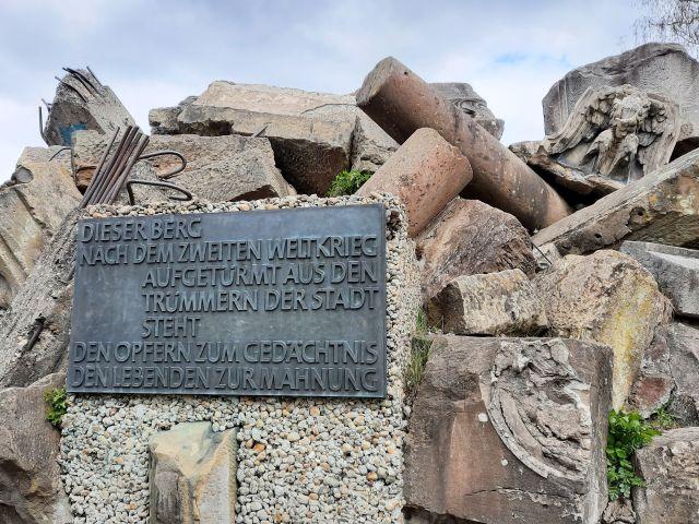 """Insdchrift auf einer dunklen Metallplatte. """"Dieser Berg, nach dem Zweiten Weltkrieg aufgetürmt aus den Trümmern der Stadt, steht den Opfern zum Gedächtnis, den Lebenden zur Mahnung"""". Die Gedenktafel ist festbetoniert. Sie ist umgeben von Trümmern, aus denen auch Metall herausragt."""