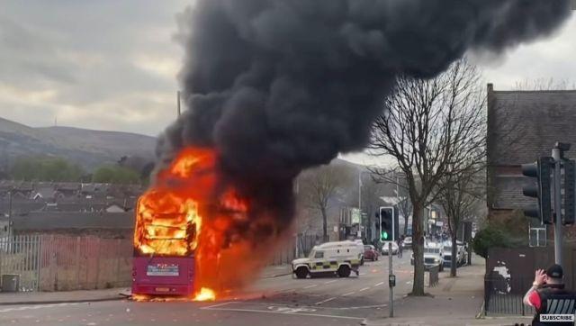 Ein roter doppelstockiger Bus brennt mitten auf der Straße. Schwarzer Rauch steigt auf. Dahinter ein Polizeifahrzeug.