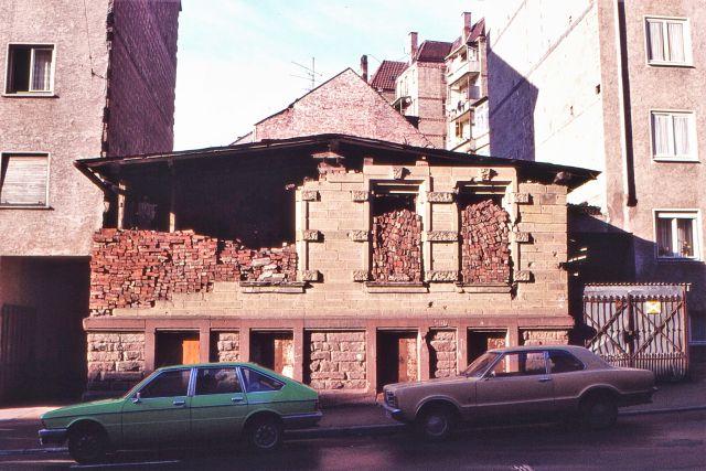 Die Ruine eines Hauses mit einem Notdach. Nur das EG ist erhalten, das 1. OG zeigt sich mit leeren Fensterbögen, in die rote Backsteine geschichtet wurde. Davor zwei Pkw.