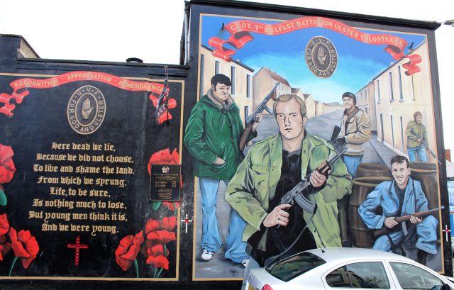 Mural in Belfast, das Männer mit Schnellfeuergewehren zeigt und an die Ulster Volunteer Force erinnert. Daneben eine Art Gedicht, in dem der Tod im Kampf als richtig dargestellt wird.