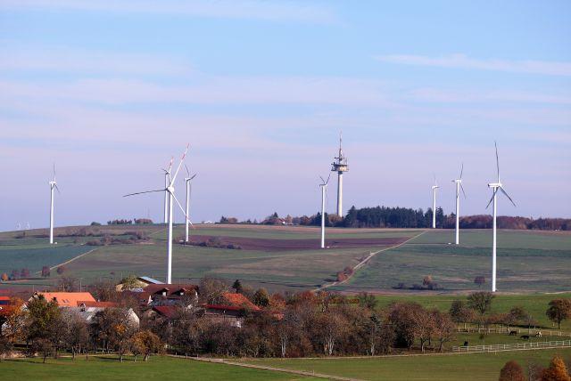 Windkraftanlagen verteilt über verschiedene Felder und Grünland. Im Hintergrund ein Fernmeldeturm.