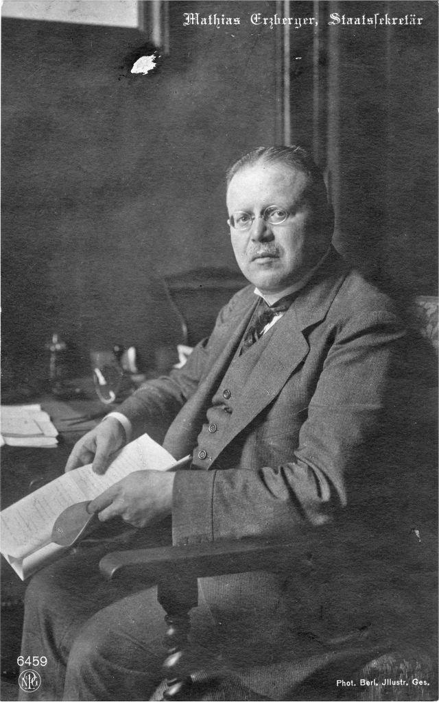 Erzberger im Anzug mit Brille an einem Schreibtisch sitzend. Er hält Unterlagen in den Händen.