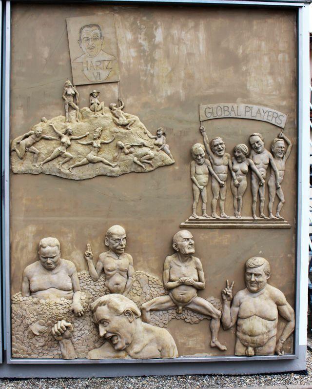 Von Peter Lenk gestaltete Wand am Bodensee. Zahllose Figuren. Angela Merkel u.a. halten ihre Hand jeweils an das Geschlechtsteil des anderen.