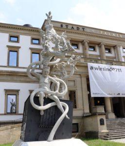 """Skulptur vor dem StadtPalais. Über dem Eingang hängt ein Transparent """"#Wir sind 0711"""". Deutlich erkennbar bei der Skulptur ist Ministerpräsident Winfried Kretschmann. Nackt bis auf ein Feigenblatt. Er kämpft mit einem ICE als Schlange dargestellt.."""