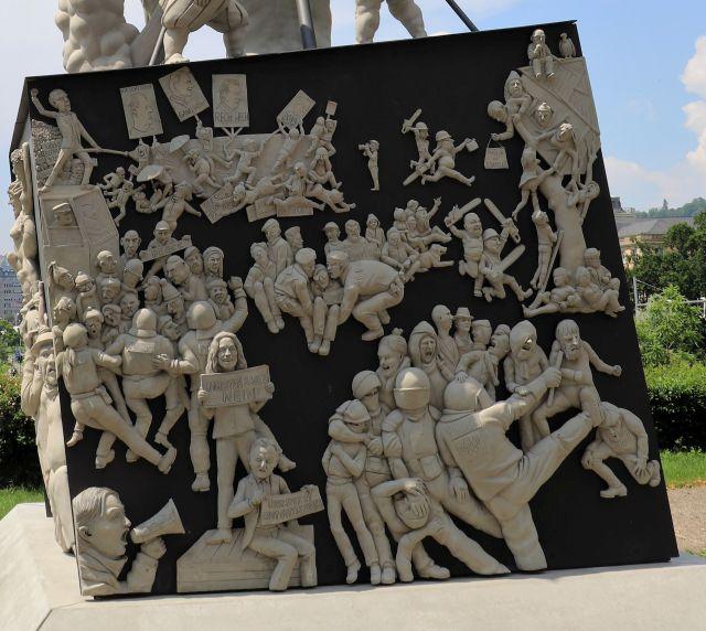 Der Quader, auf dem sich die Skulptur nach oben reckt, ist mit zahllosen kleinen Figuren bedeckt.